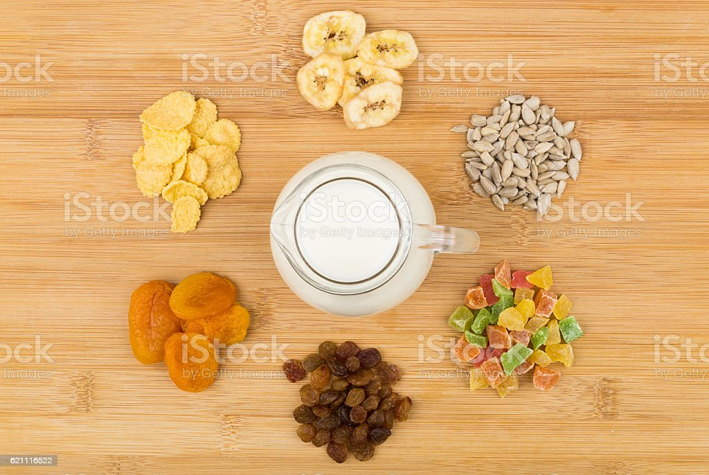 Jug milk and heap of ingredients for muesli on table stock photo