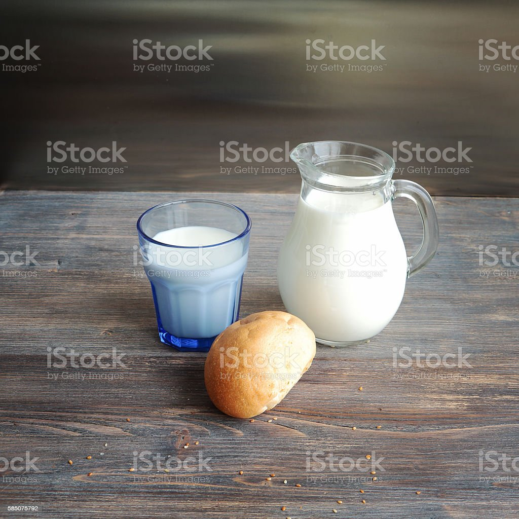 Jug of milk, glass of milk and bread roll on a wooden table. Special...