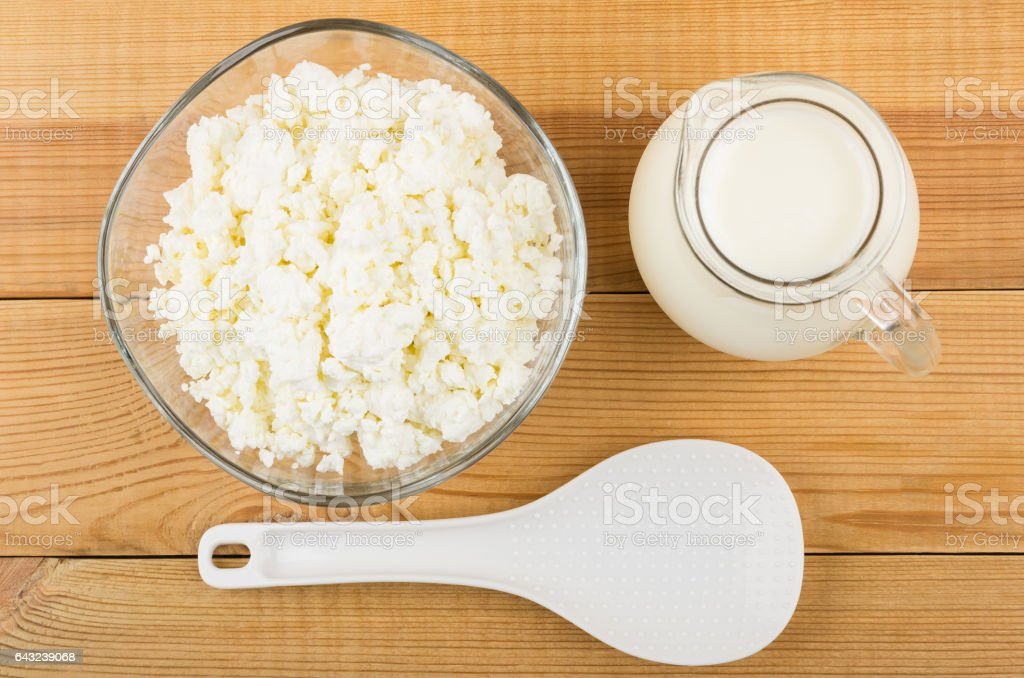 Jug of milk, plastic spoon and bowl with cottage cheese stock photo
