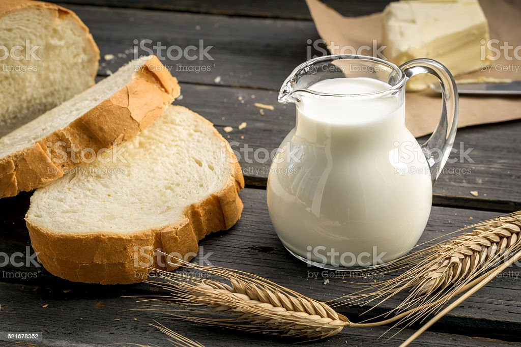 Jug of milk with freshly baked bread and wheat ears stock photo