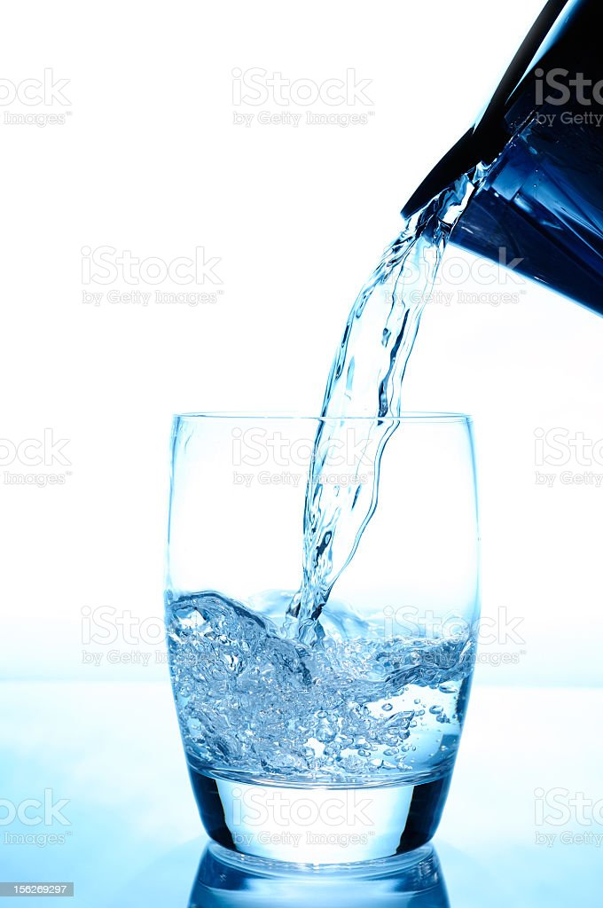 A jug pouring crisp clear water in a glass royalty-free stock photo