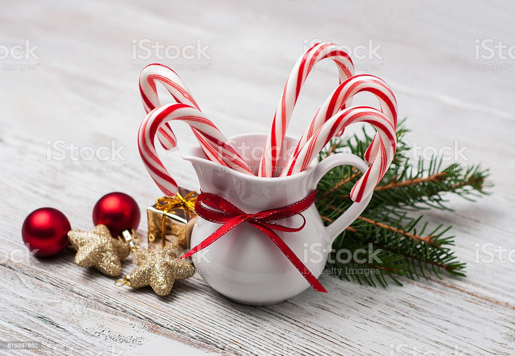 Jug with christmas candy canes on a wooden table stock photo