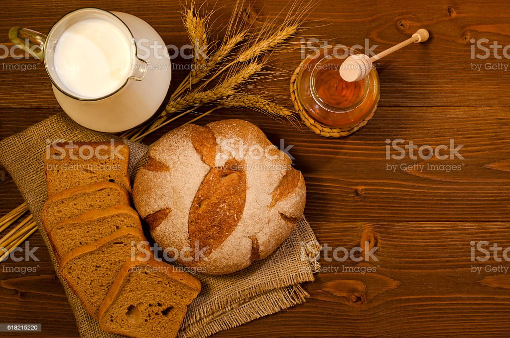 Jug with milk, rye bread, ears, honey, on wooden table stock photo