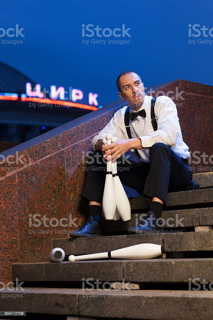 Juggler sitting on the steps near the circus. stock photo