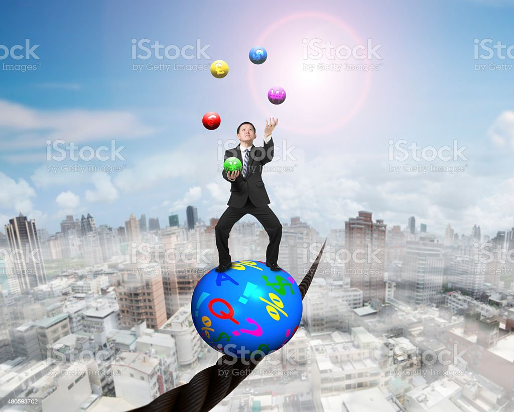 Juggling businessman standing on symbols ball balancing on wire stock photo