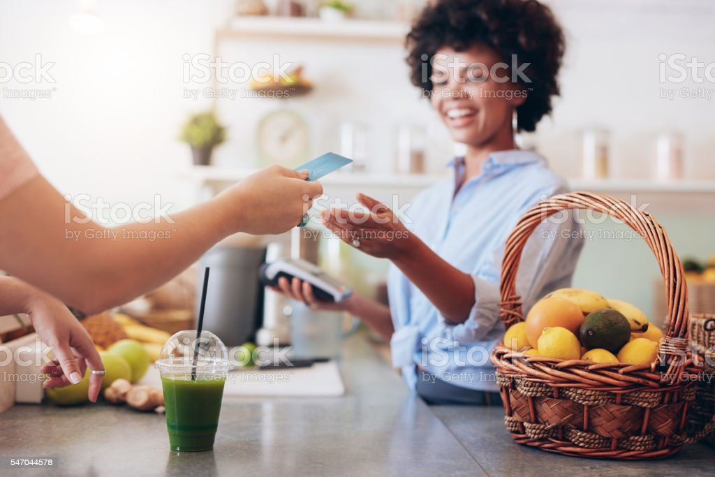 Juice bar owner taking payment from customer stock photo