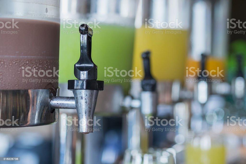 Juice dispenser of ice chocolate, guava, pineapple and orange juice stock photo