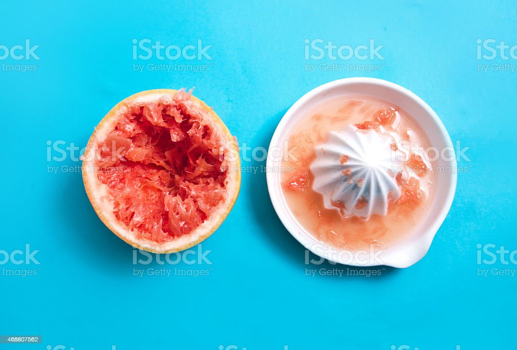 Juiced Grapefruit with a squeezer stock photo