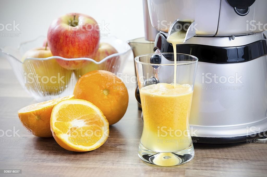 Juicer and orange juice. Fruits in background stock photo