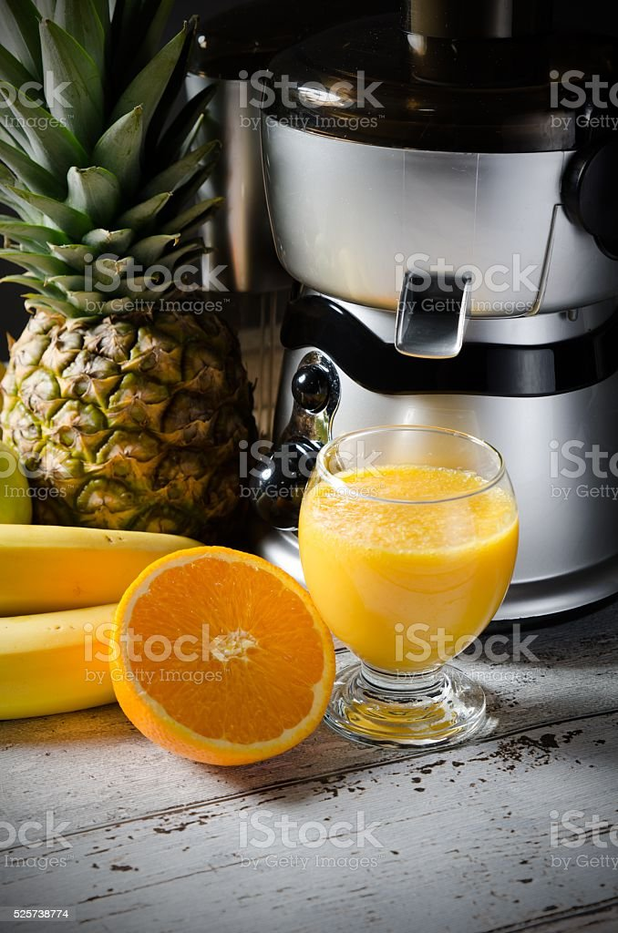 Juicer and orange juice in glass on wooden desk stock photo