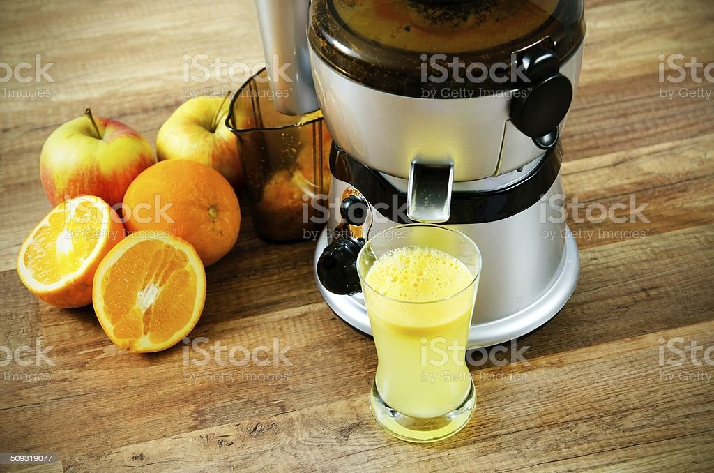 Juicer and orange juice on wooden background stock photo