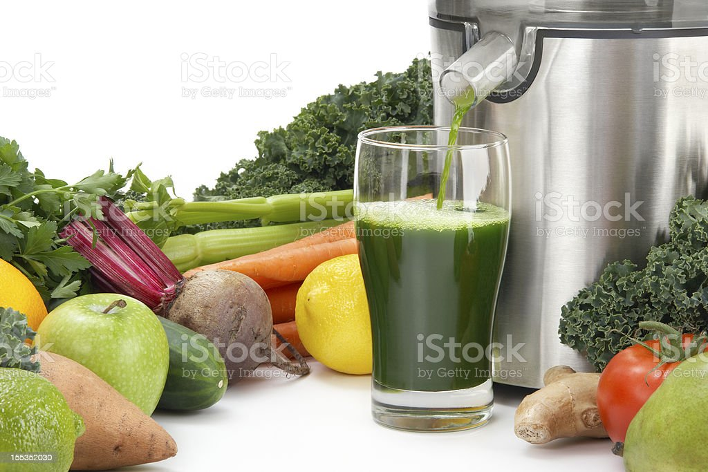 Juicer pouring juice into glass surrounded by vegetables stock photo