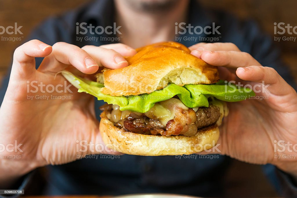 Juicy Bacon Cheese Burger in Hands About to Be Eaten stock photo