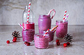 Juicy berry smoothies in glass jars on marble background.