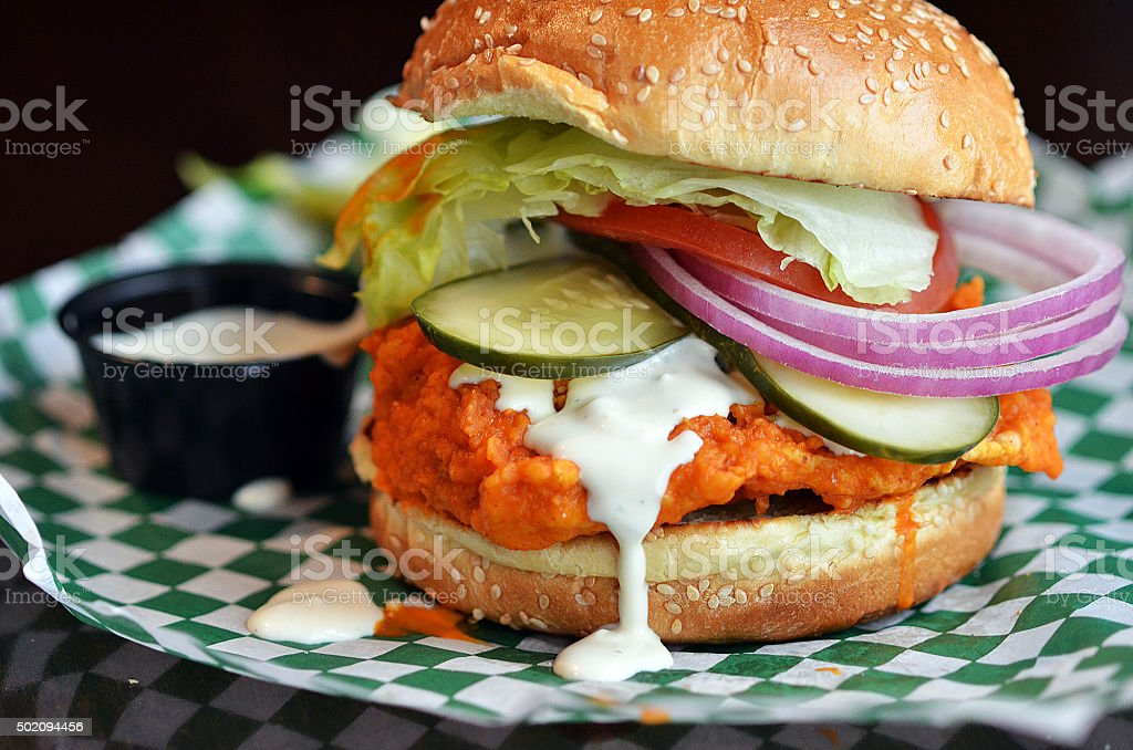 Juicy Buffalo Chicken Sandwich with Pickles, Red Onions, Ranch Dressing stock photo