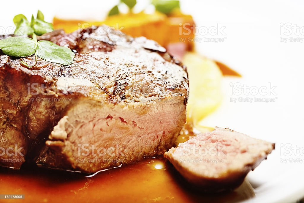 Juicy fillet steak, sliced open, in pool of meat juices stock photo