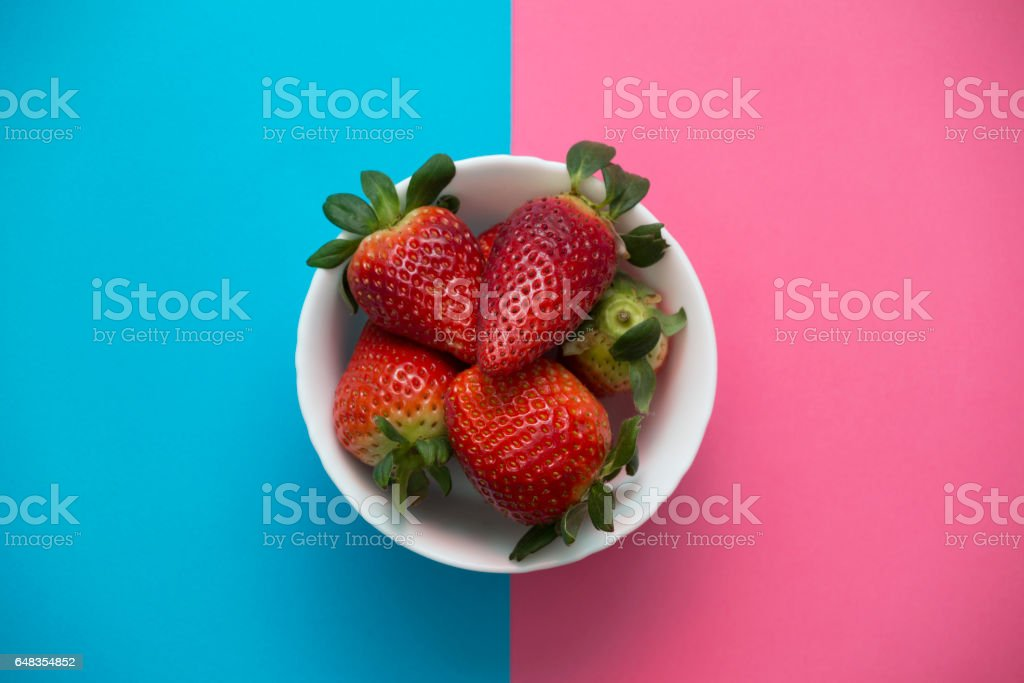 Juicy, fresh, ripe strawberries in a bowl on rose quartz and serenity blue background stock photo