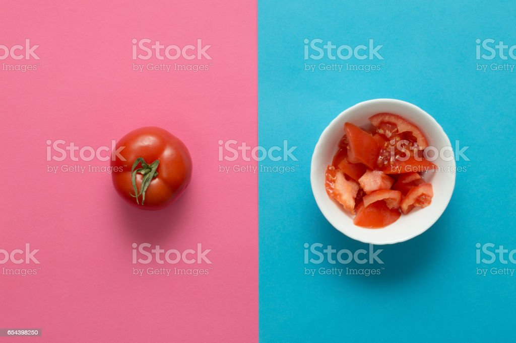 Juicy, fresh, ripe tomato in a bowl on rose quartz and serenity blue background. Directly above view. stock photo