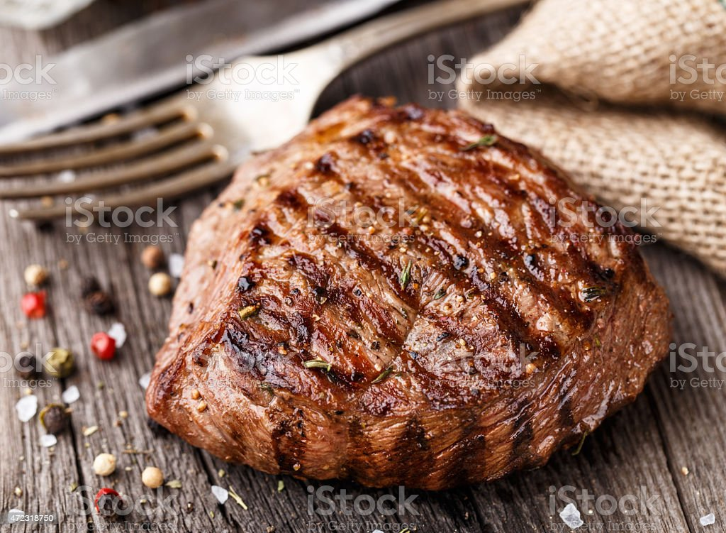 Juicy grilled steak with whole pepper on a wooden table stock photo