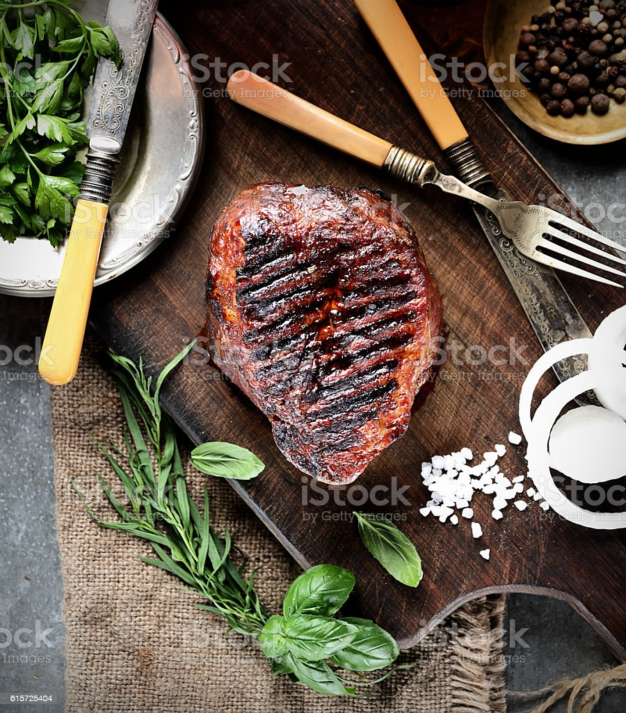 juicy grilled steaks on a cutting board stock photo