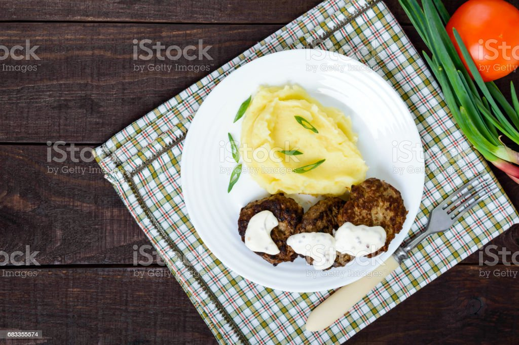 Juicy liver cutlet with sauce and mashed potatoes on a white plate. The top view stock photo