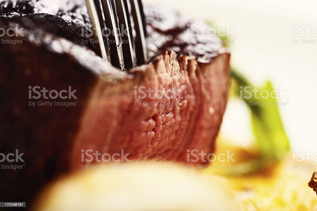 Juicy, medium-rare steak being sliced stock photo