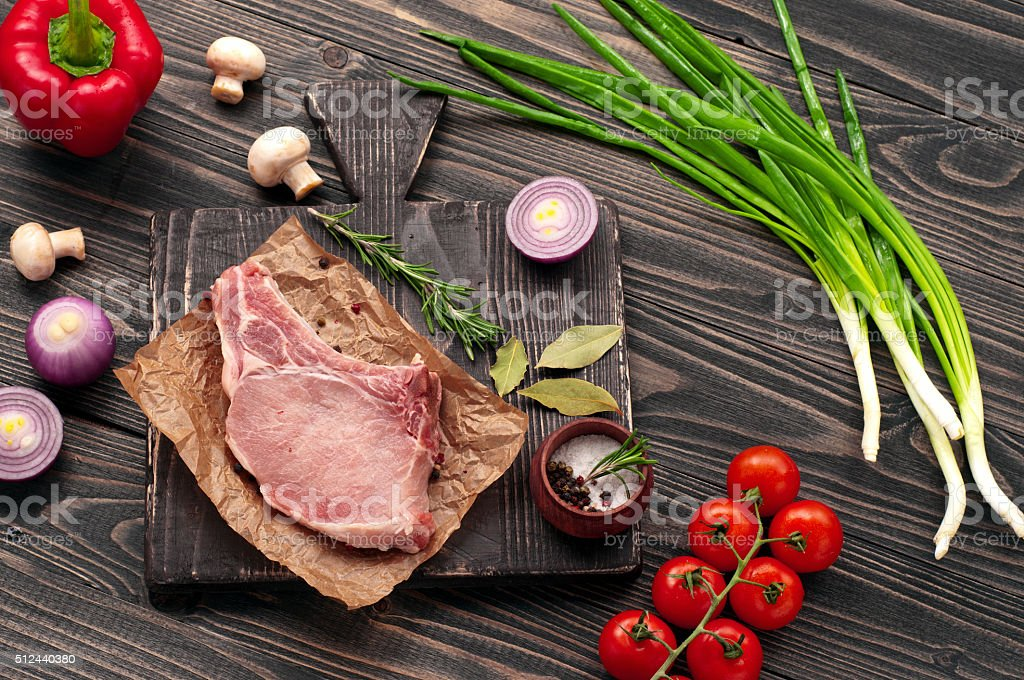 juicy piece of meat on the bone with vegetables stock photo