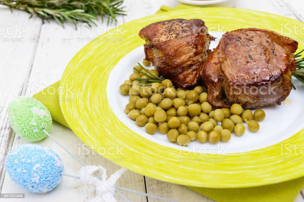 Juicy pork medallions wrapped in bacon, serve with green peas and a sprig of rosemary on a plate. stock photo