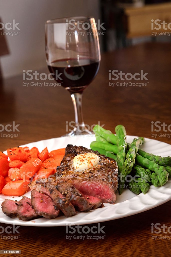 Juicy Rare Ribeye Steak With Vegetables And Wine stock photo