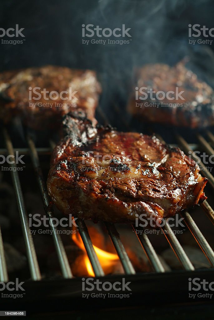 Juicy Rib-Eye Cooking on a Grill with Flames in Background royalty-free stock photo