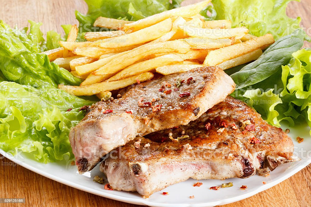 Juicy roasted pork steak with french fries and spices stock photo