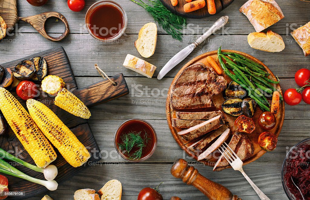 Juicy sliced grilled beef steak with various grilled vegetables stock photo