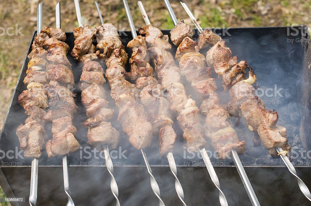 Juicy slices of meat with sauce prepare on fire royalty-free stock photo