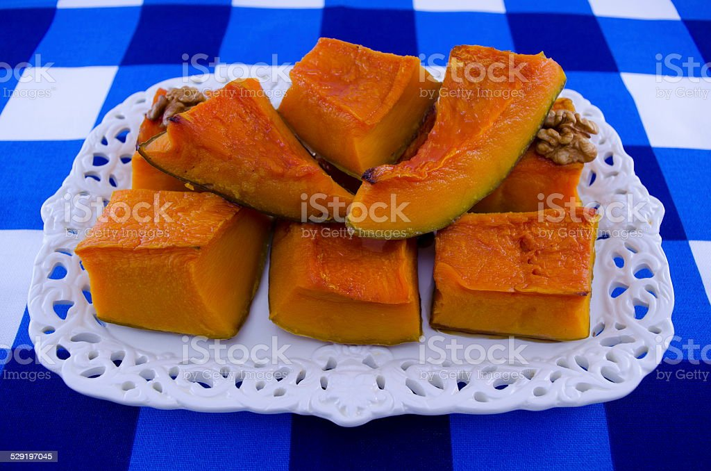 Juicy squash cut into pieces on a white tray royalty-free stock photo