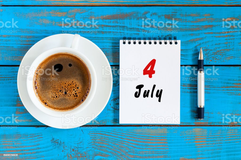 July 4th. Day of the month 4 , calendar on blue wooden table background with morning coffee cup. Summer concept stock photo