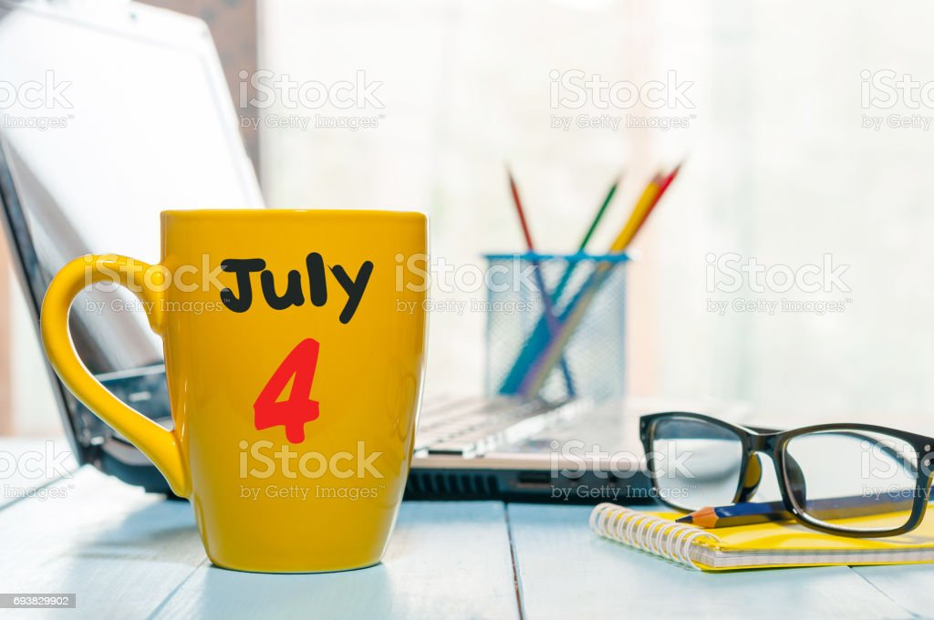 July 4th. Day of the month 4 , color calendar on yellow morning coffee cup at business workplace background. Summer concept. Empty space for text stock photo