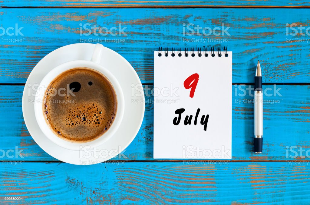 July 9th. Day 9 of month, calendar on blue wooden table background with morning coffee cup. Summer concept stock photo