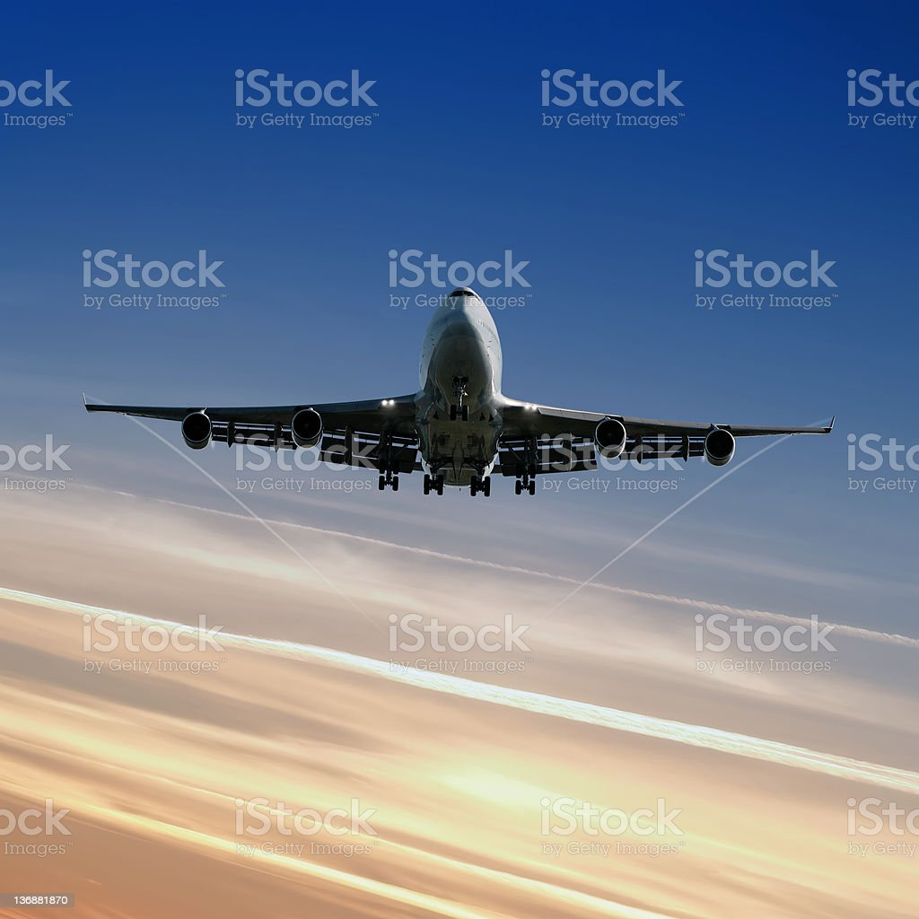 XL jumbo jet airplane landing at dusk royalty-free stock photo