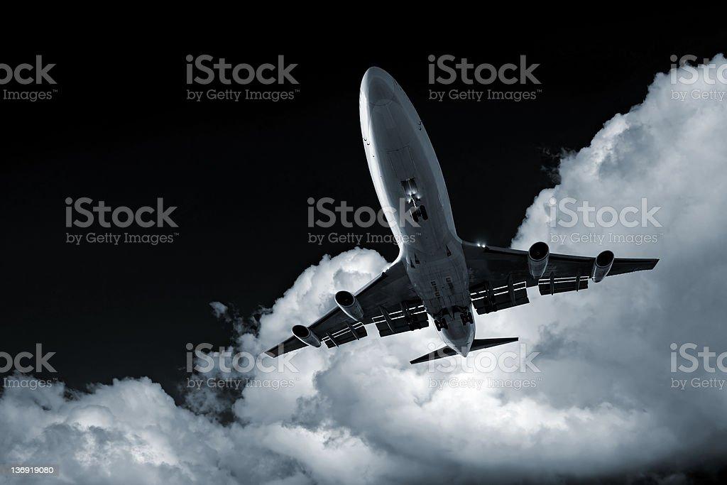 XL jumbo jet airplane landing at night royalty-free stock photo