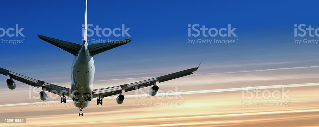XL jumbo jet airplane landing at sunset royalty-free stock photo