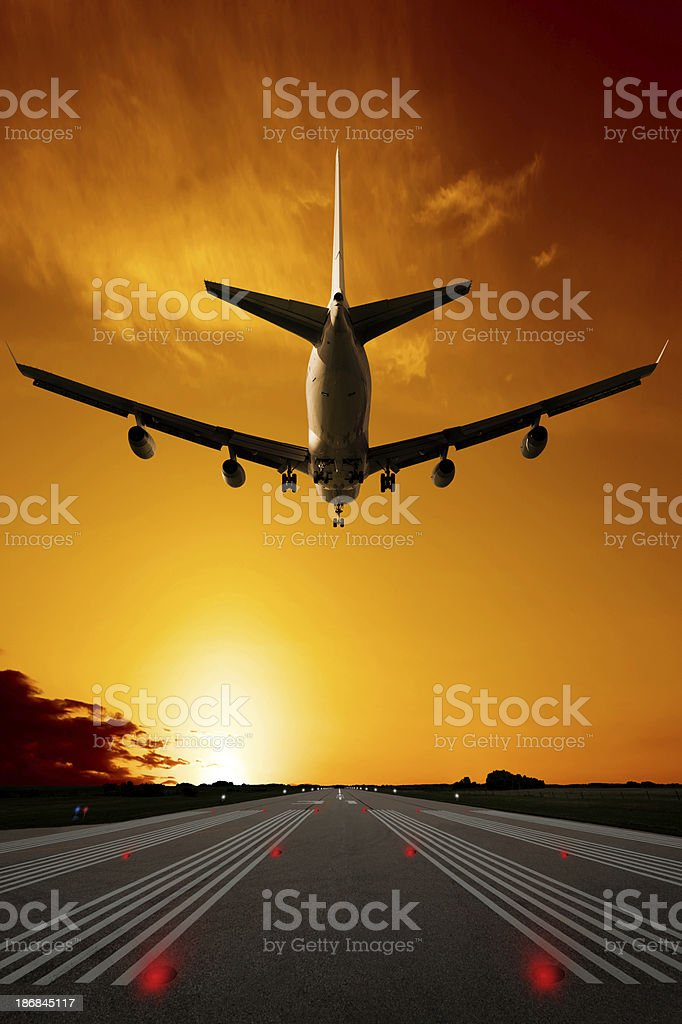 XXXL jumbo jet airplane landing at sunset royalty-free stock photo