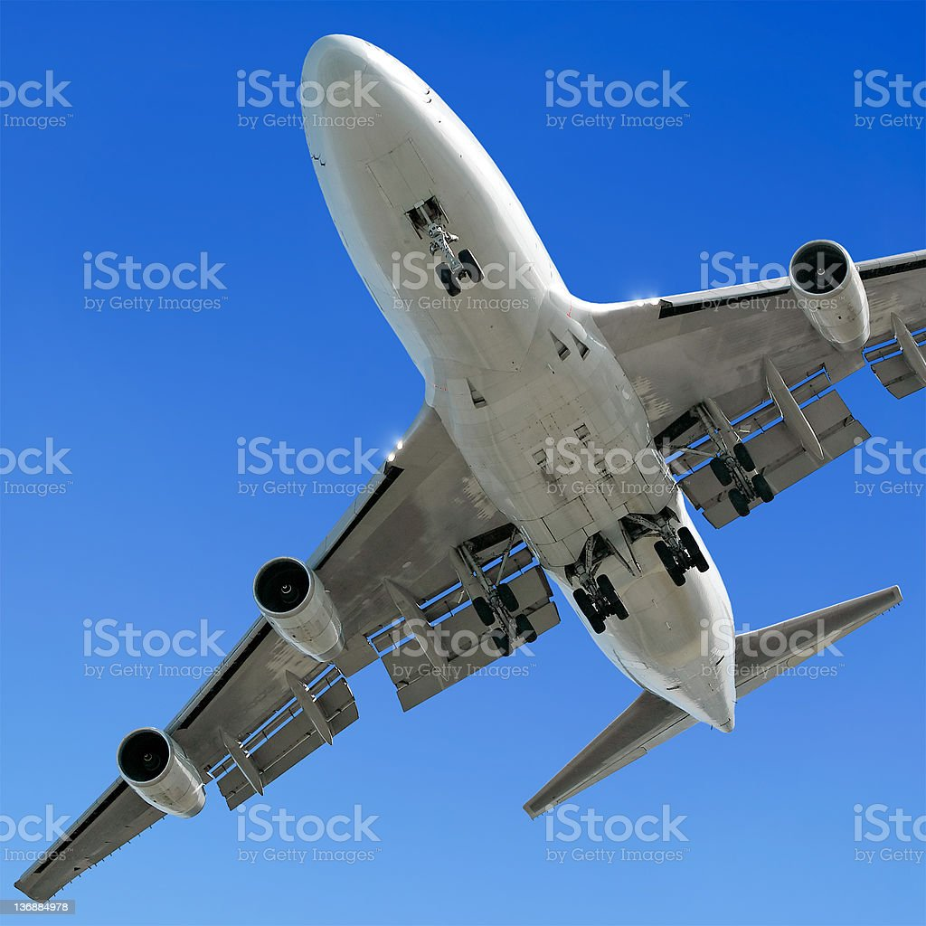 jumbo jet airplane landing in clear blue sky royalty-free stock photo