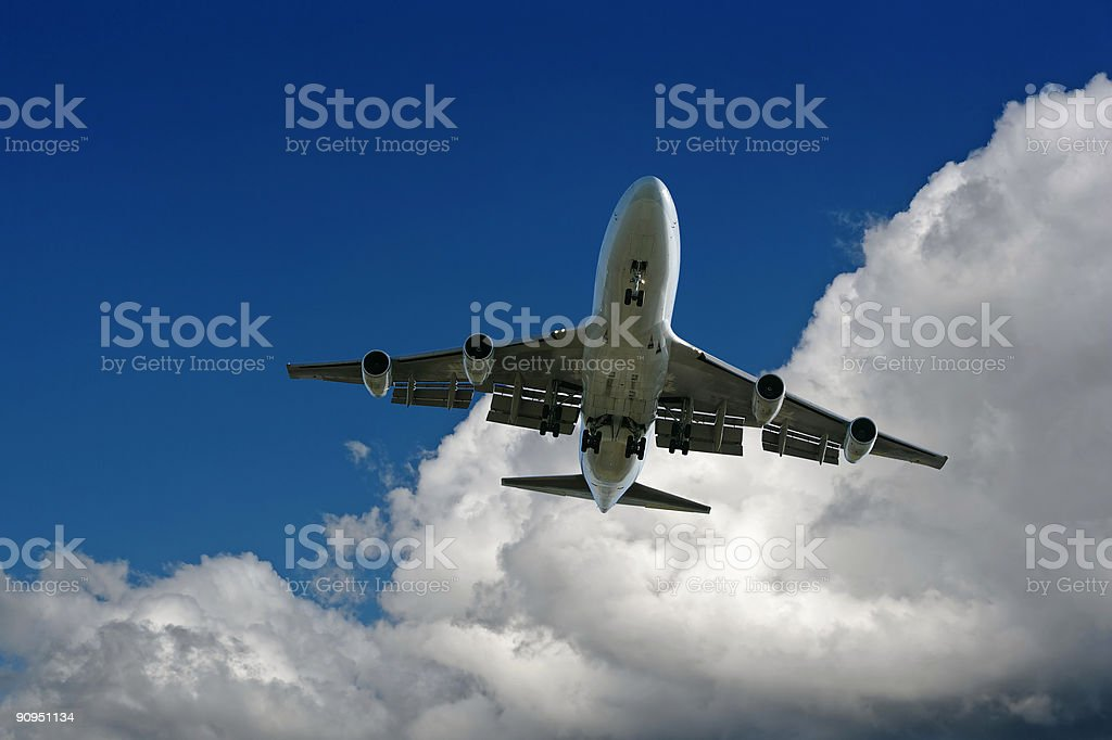 XXL jumbo jet airplane landing in cloudy sky royalty-free stock photo