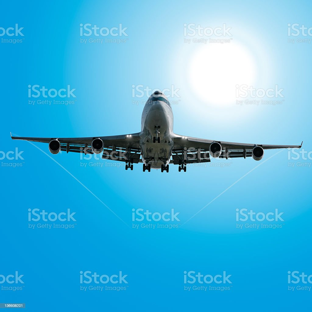jumbo jet airplane landing in sunny sky royalty-free stock photo