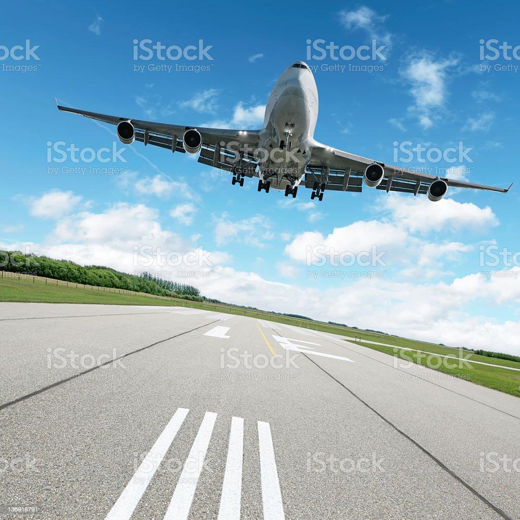 XL jumbo jet airplane landing on runway royalty-free stock photo