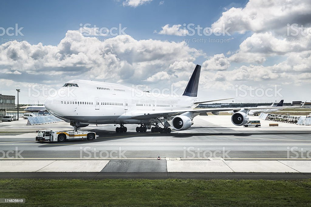 A jumbo jet gets parked nearby a runway with white clouds stock photo