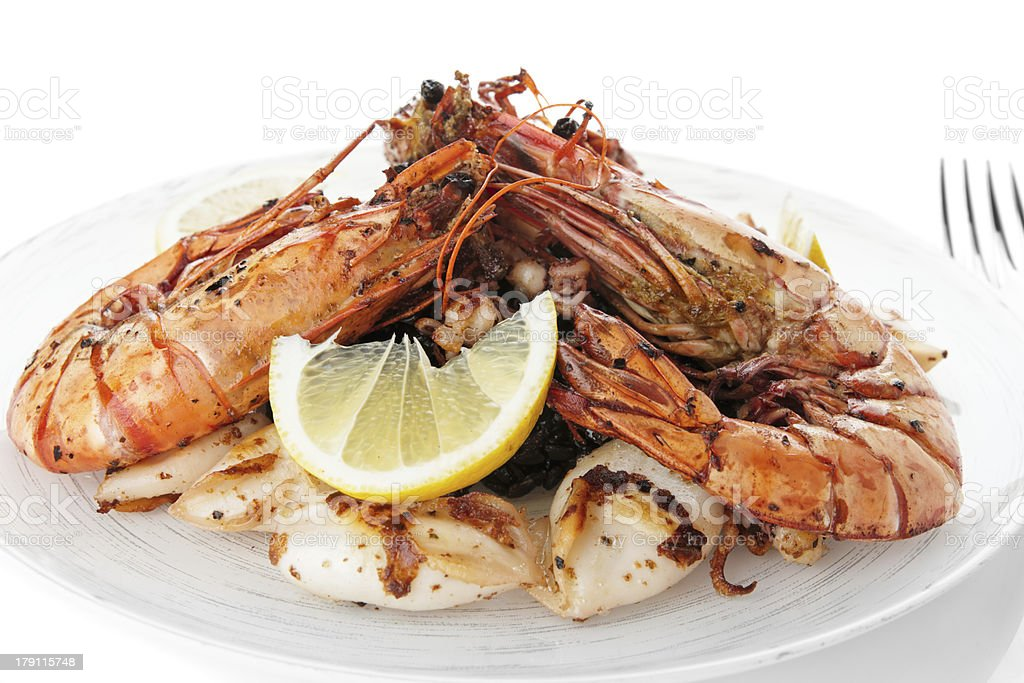 Jumbo prawns and grilled squids with black rice isolated royalty-free stock photo