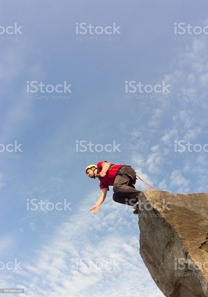Jump off the cliff with a rope. stock photo