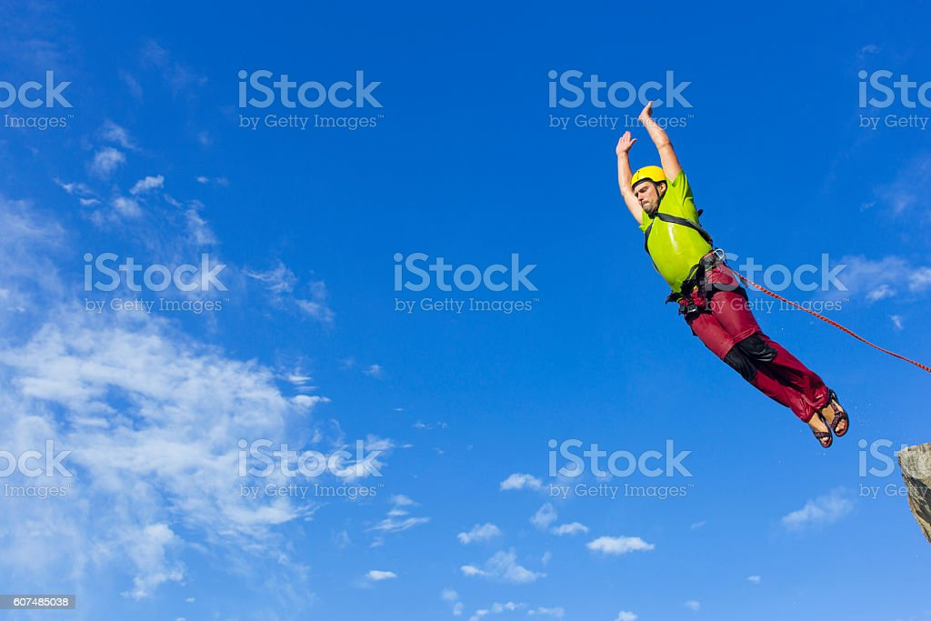 Jump rope from a high rock in the mountains. stock photo