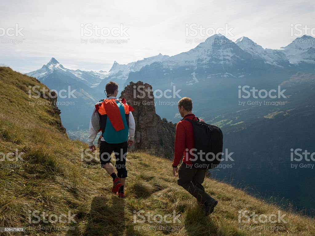 BASE jumpers approach edge of cliff stock photo